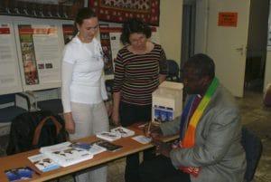 zwei Frauen stehen hinter einem Tisch mit Prospekten. Ein schwarzer Mann schreibt auf einen Zettel. Er ist Bischof in Tansania.